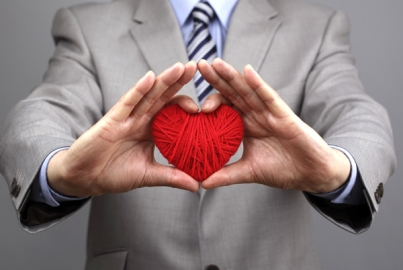 Businessmen is holding out a red heart